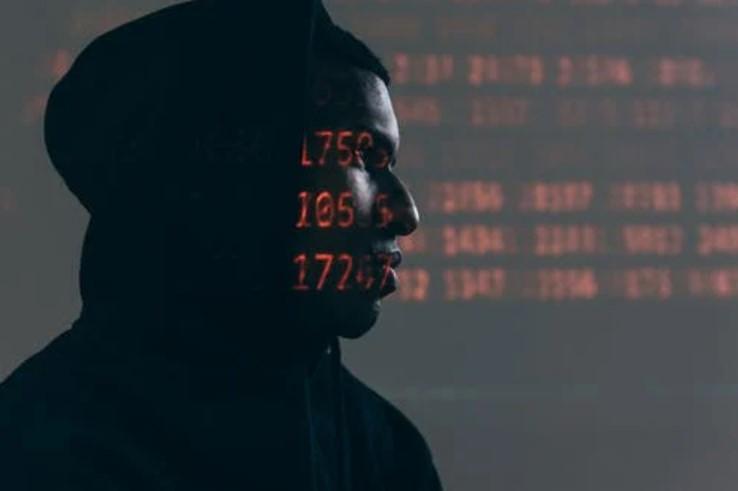 Ciberbullying.adolescente con capucha y numeros hacking.
