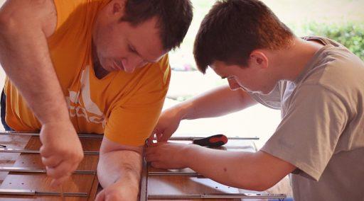 Padre e hijo construyendo un mueble juntos.