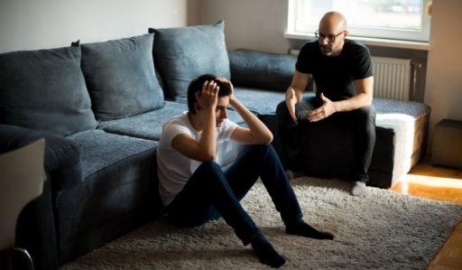 Padre regañando a su hijo adolescente