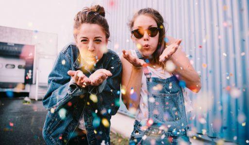 2 amigas adolescentes soplando purpurina a la camara