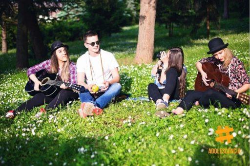 Grupo adolescente sentados en el parque tocando instrumentos y haciendo fotografías